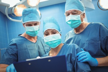 Team of surgeons discussing over clipboard in operation theater