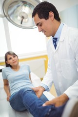 Doctor examining a female patients leg