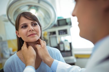 Doctor examining a female patients neck
