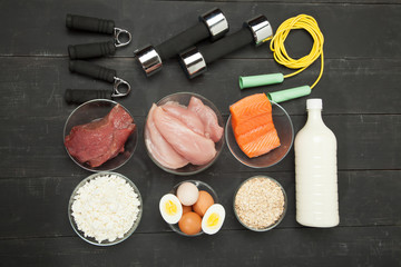 Proteins and dumbbells. Fish, cheese, eggs, meat, chicken  heart on a black wooden background