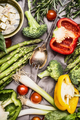 Various colorful vegetables ingredients with cooking spoon and feta cheese for tasty cooking, top view. Healthy vegetarian food or diet nutrition concept