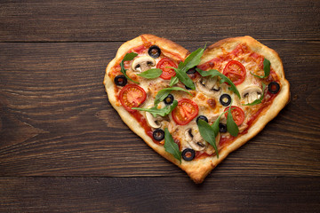 Heart shaped pizza with chicken and mushrooms on dark wooden vintage background.