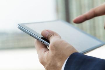 Hands of businessman working on digital tablet outdoor