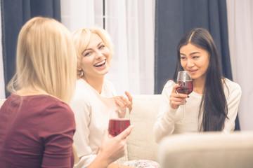 Toned picture of cheerful friends businesswomen having party at home. Beautiful ladies smiling and communicating about every day life: work, home, men.