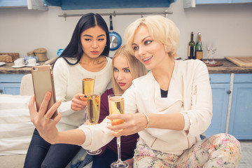Toned picture of beautiful friends girls posing for mobile or smart phone's camera. Real business ladies having party with champagne at home. Home party concept.