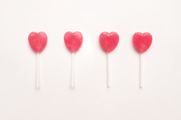 four Pink Valentine's day heart shape lollipop candy arrange on empty white paper background. Love Concept. Knolling top view. Minimalism colorful hipster style.