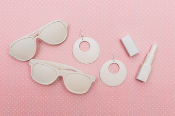 Flat lay set of two sunglasses, earrings and lipstick on pink background. items painted white color
