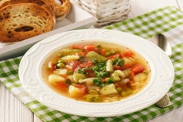 Vegetarian vegetable soup on wooden background.