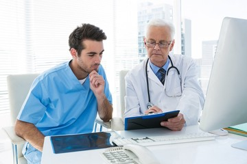 Surgeon and doctor discussing over clipboard