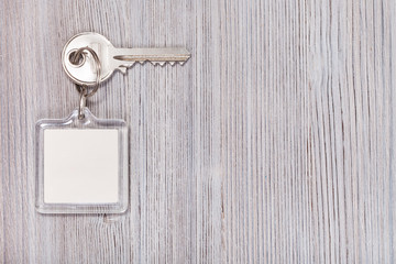 key with key chain on wooden background
