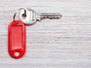 key with red key chain on wooden background