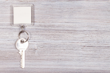 key with key chain on wooden surface