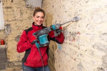 Engagierte Handwerkerin mit Stemmhammer an Backsteinmauer in Roh