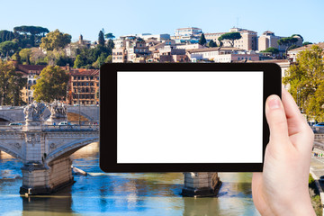 tourist photographs bridge on Tiber River in Rome
