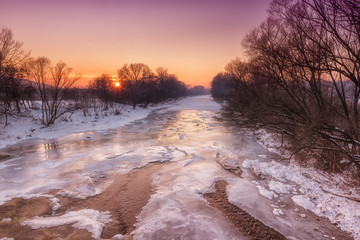 Beautiful pink sunset over a frozen river, winter landscape