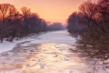 Frozen river, winter landscape in soft pink sunset light