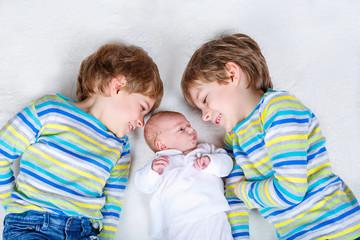 Two happy little preschool kids boys with newborn baby girl