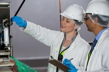 Technicians examining meat processing machine