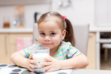 Child girl drinking milk in the kitchen at home
