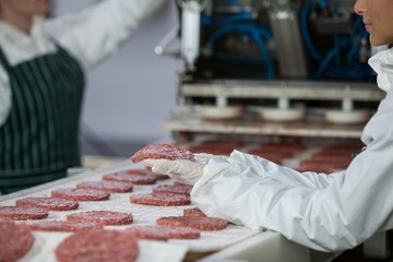 Female butcher processing hamburger patty