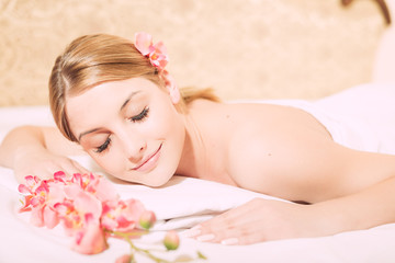 Attractive woman laying on massage spa bed white background, portrait closeup