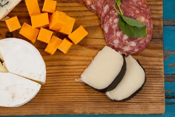 Variety of cheese with ham on chopping board