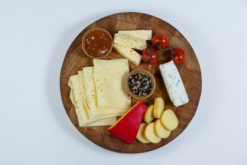 Different types of cheese, tomatoes and bowl of jam