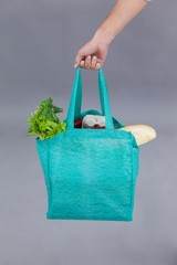 Hand of a woman holding grocery bag