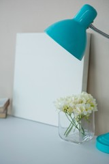 Picture frame with table lamp and flower vase