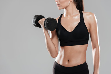 Cropped image of Sporting woman using dumbbell