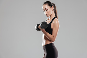 Side view of Young Sporting woman using dumbbell