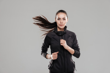 Attractive fitness lady running over grey background.