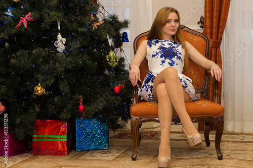 Sexy Charming Woman Sitting On Chair With Legs Crossed