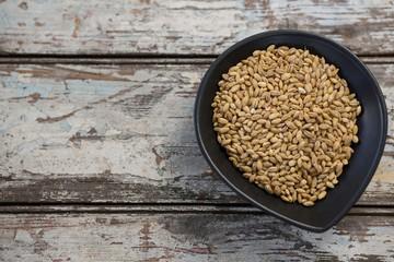Wheat grains in black bowl