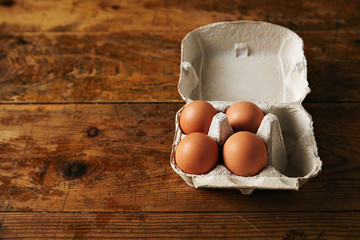 Presentation of opened recyclable egg carton for six eggs containing four big ecological eggs on a rough rustic brown wooden table