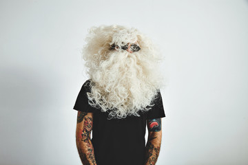 Portrait of tattooed brutal male weared blank black t-shirt and Santa's hair and beard wig turds his head around, isolated on white wall