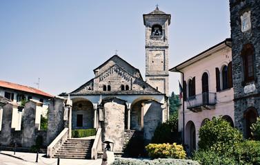la piazza del paese degli ombrellai  con chiesa romanica e un monumento
