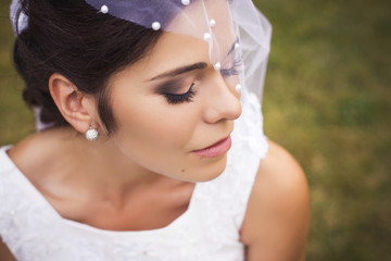 Beautiful bride preparing to get married in white dress and veil