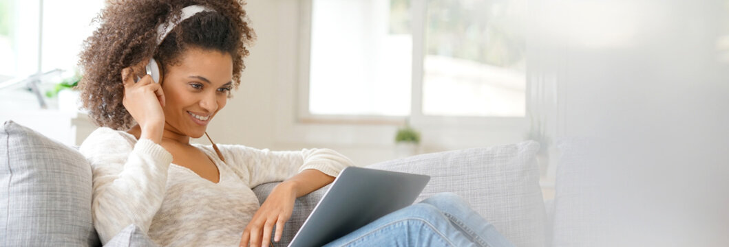Cheerful woman making a videocall on laptop computer