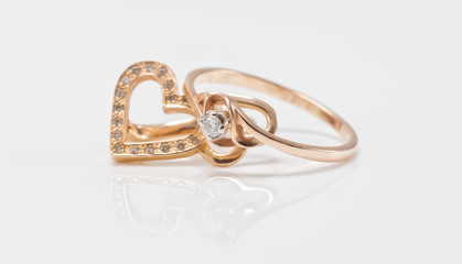 Gold earrings in the shape of a heart and a thin ring with diamo