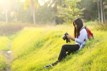 Young woman holding a digital camera, checking a picture result, carrying a backpacker, sitting on a grass or lawn - Traveler concept