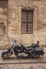 Black retro motorcycle. Motorbike near old wall. Respect the classics.
