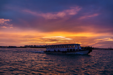 Local ferry swimming near Male town, Maldives at sunset