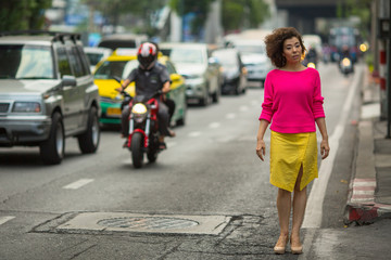 Asian woman on a busy highway. Urban portrait.