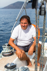A man sits on his sailing yacht.