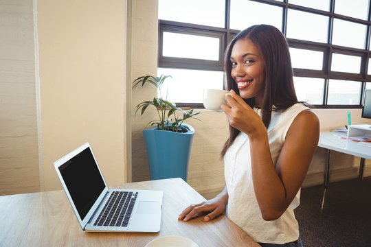 Smiling woman sitting at desk and having coffee in office