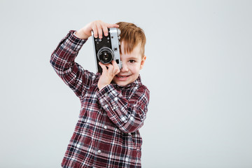 Smiling little boy taking photos with old vintage camera