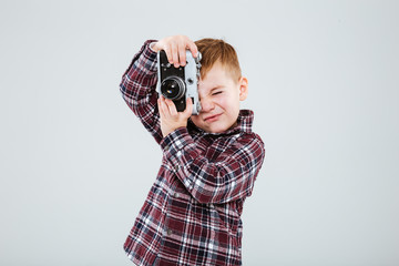 Little boy standing and taking pictures with vintage photo camera