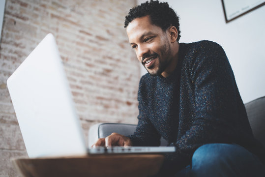 Happy african man dressed in grey pullover and typing on laptop,smiling while sitting  the sofa.Blurred background.