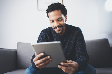 Selective focus.Attractive bearded African man reading news on digital tablet while sitting  sofa in his modern studio.Concept of young business people working at home.Blurred background.